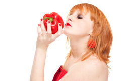 Model smelling red pepper. Portrait of young attractive redhead in red dress holding fresh red pepper, isolated on white background Stock Photo