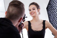 Model smiling to the photo. Model in black dress smiling for a photo Stock Photography