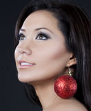 Model with sparkling christmas ornament earrings. A beautiful brunette hair model poses with a  red sparkling christmas ornamant earring Stock Image