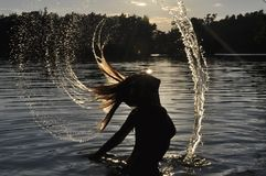 Model splashing water with her hair at sunset Royalty Free Stock Images