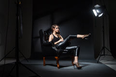 Model in spotlight posing on black leather chair in studio Stock Images