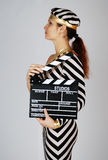 Model in stripy dress and cap at shooting. Model in stripy black-and-white dress and cap stands sideways, holds cinematographic plank stock photo
