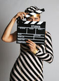 Model in stripy dress and cap at shooting. Model in stripy black-and-white dress and cap looks narrowly, face closed with cinematographic plank stock image