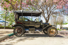 Model T (1915) at Pi Day Car Show. Restored vintage Model T (1915) on display at Pi Day Classic Car Show. Partially shaded by pink flowered trees. Right side stock photos