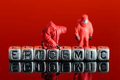 Model team in chemical suits with the word epidemic on beads. Miniature scale model team in chemical suits with the word epidemic on beads Stock Photo