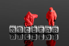 Model team in chemical suits with the word nuclear on beads Royalty Free Stock Photos