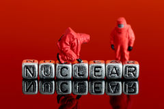 Model team in chemical suits with the word nuclear on beads Stock Photography