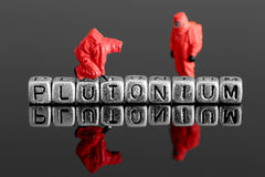 Model team in chemical suits with the word plutonium on beads. Miniature scale model team in chemical suits with the word plutonium on beads Royalty Free Stock Images