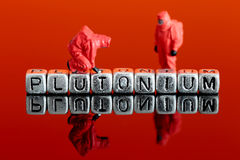 Model team in chemical suits with the word plutonium on beads. Miniature scale model team in chemical suits with the word plutonium on beads Stock Photos