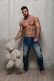 Model with teddy bear. Muscled male model with a teddy bear Stock Images