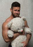Model with teddy bear. Muscled male model with a teddy bear royalty free stock images