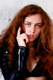 Model tests. Beautiful redhead girl with curly hair. Natural color. The bold and the harmful look, a black leather Royalty Free Stock Image
