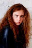 Model tests. Beautiful redhead girl with curly hair. Natural color. The bold and the harmful look, a black leather Stock Images