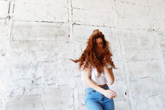 Model tests. Beautiful redhead girl with curly hair. Natural color. Dancing and moving on the background of light brick Royalty Free Stock Photos