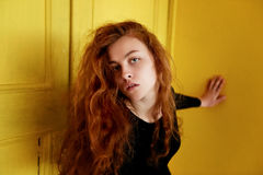 Model tests. Beautiful redhead girl with curly hair.Natural color. Great contrast with yellow wooden doors. Model tests. Beautiful redhead girl with curly hair stock photo