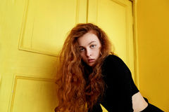 Model tests. Beautiful redhead girl with curly hair.Natural color. Great contrast with yellow wooden doors. Model tests. Beautiful redhead girl with curly hair royalty free stock image