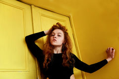 Model tests. Beautiful redhead girl with curly hair.Natural color. Great contrast with yellow wooden doors. Model tests. Beautiful redhead girl with curly hair royalty free stock photos