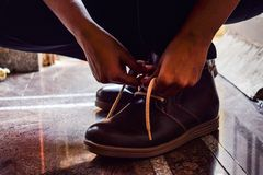 Model tiding laces of his brown color boots royalty free stock photo