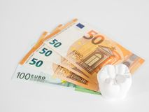 The model tooth szeht on the money in euro currency. On the white background Stock Photos