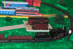 Model of a toy railway with a cargo train. Older and modern transport Royalty Free Stock Photos