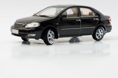 Model Toyota Corolla. Isolated black Toyota Corolla miniature replica reflecting on white background Stock Photos