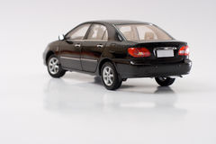 Model Toyota Corolla. Rear view of black Toyota Corolla miniature replica with shadow, isolated and reflecting on glossy white background Stock Photo