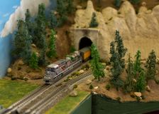 A model train emerges from a tunnel in a mountain with pine trees to either side.  royalty free stock photography