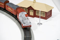 Model train passing house. Model train pulling goods wagons on single track passing a brown and cream house or ticket office stock photography