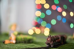Model train on railway with colorful bokeh. Locomotive on track Stock Photography
