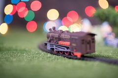 Model train on railway with colorful bokeh. Locomotive on track Royalty Free Stock Photo