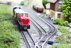 Model train standing by a train station. Train model at railway station Stock Image
