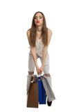 Model trying to lift shopping bags Stock Photos