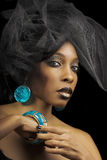 Model with turquoise jewelry. Portrait of black female model wearing turquoise-colored earrings, bracelet, and eyeshadow with tulle fabric on head Stock Photography