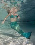 Model underwater in a pool wearing a mermaids tail. Royalty Free Stock Photo