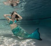 Model underwater in a pool wearing a mermaids tail. Royalty Free Stock Images
