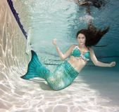 Model underwater in a pool wearing a mermaids tail. Royalty Free Stock Photography