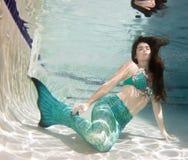 Model underwater in a pool wearing a mermaids tail. Stock Image