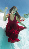 Model Underwater in a Red Dress Stock Images