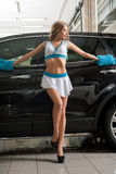 Model in uniform washing car at car wash service royalty free stock image