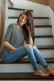 Model van de Milings het Kaukasische jonge mooie vrouw met slordig lang haar in gescheurde jeans en gestreepte t-shirt stock afbeelding
