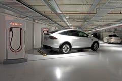 Model X van de Tesla insteek elektrisch auto geladen door Supercharge stock foto