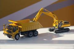 Model van een vrachtwagen en een graafwerktuig op de tribune Stock Afbeelding