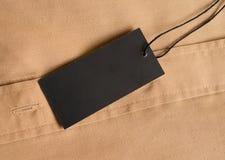 Model van het etiket het zwarte prijskaartje op beige overhemd Stock Fotografie
