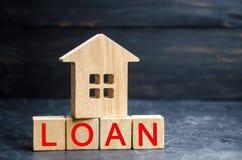 Model van het huis en de inschrijving 'Lening ' Het kopen van een huis in schuld Familieinvestering in onroerende goederen en ris stock afbeelding