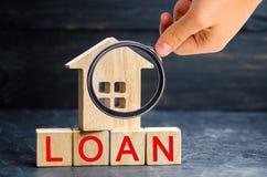 Model van het huis en de inschrijving 'Lening ' Het kopen van een huis in schuld Familieinvestering in onroerende goederen en ris stock fotografie