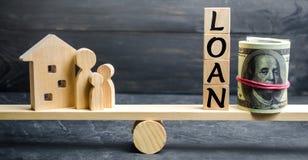 Model van het huis, geld en de inschrijvings` Lening ` op de schalen Het kopen van een huis in schuld Familieinvestering in onroe stock afbeeldingen