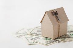 Model van kartonhuis met sleutel en dollarrekeningen Woningbouw, onroerende goederen lening, kosten om een nieuw huis te huisvest Stock Afbeelding