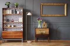 Model van leeg gouden kader boven kabinet in het grijze retro leven ro royalty-vrije stock afbeeldingen