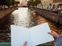 Model van leeg notitieboekje in vrouwelijke handen op de achtergrond van de stadsrivier royalty-vrije stock foto