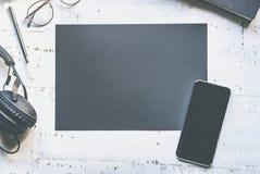 Model van leeg zwart document blad, mobiele telefoon, oogglazen, hoofdtelefoons op natuurlijk wit authentiek houten bureau stock afbeeldingen